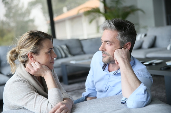 Mature couple talking to each other in sofa